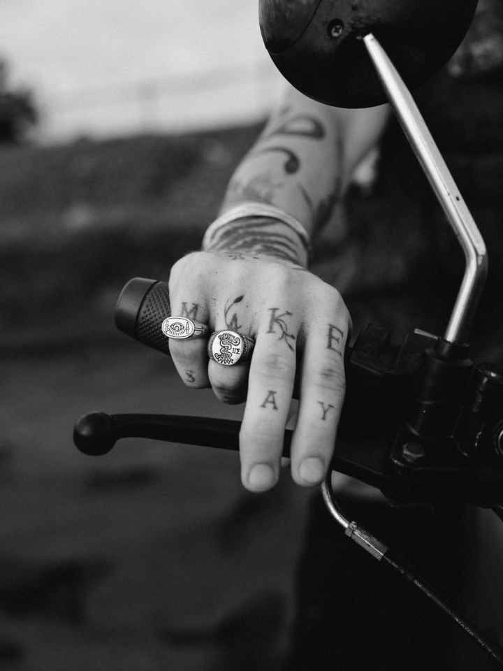 grayscale photo of person with rings and tattoos